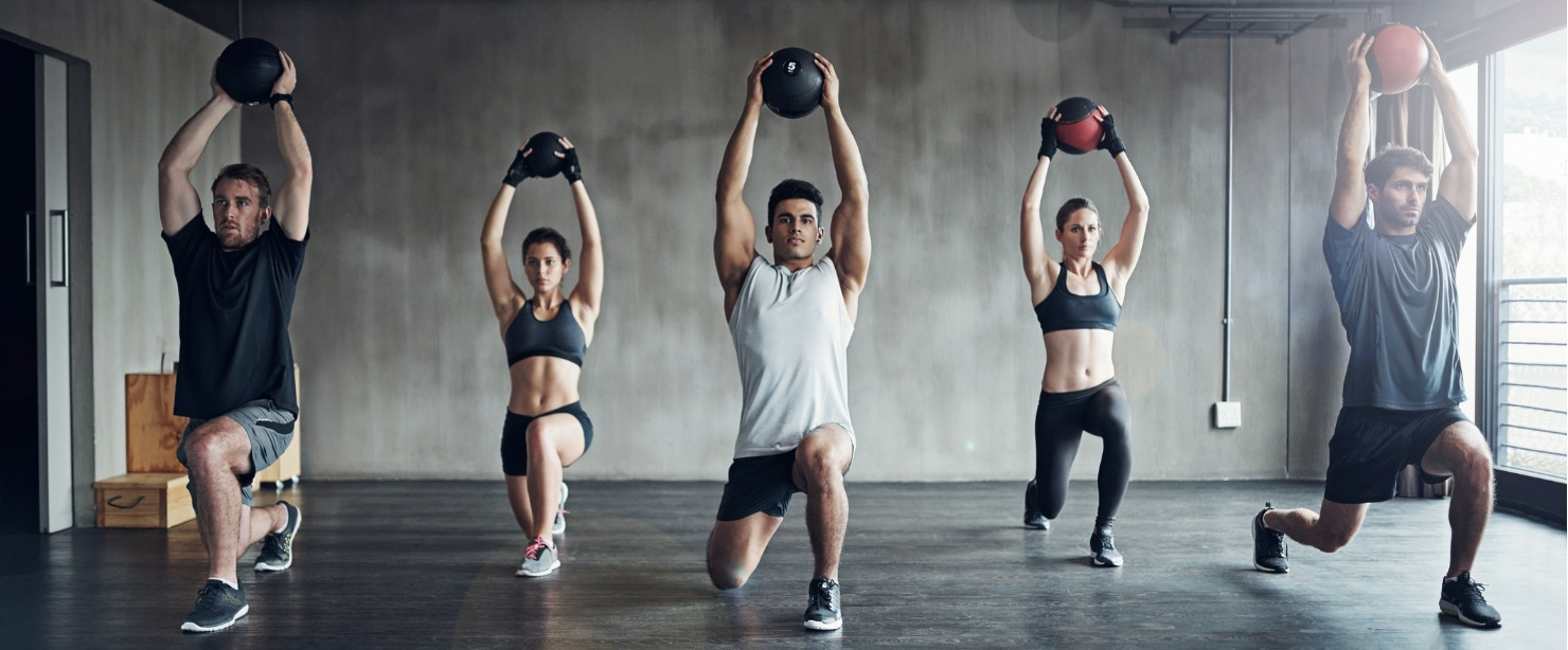 group exercise class doing overhead lunges