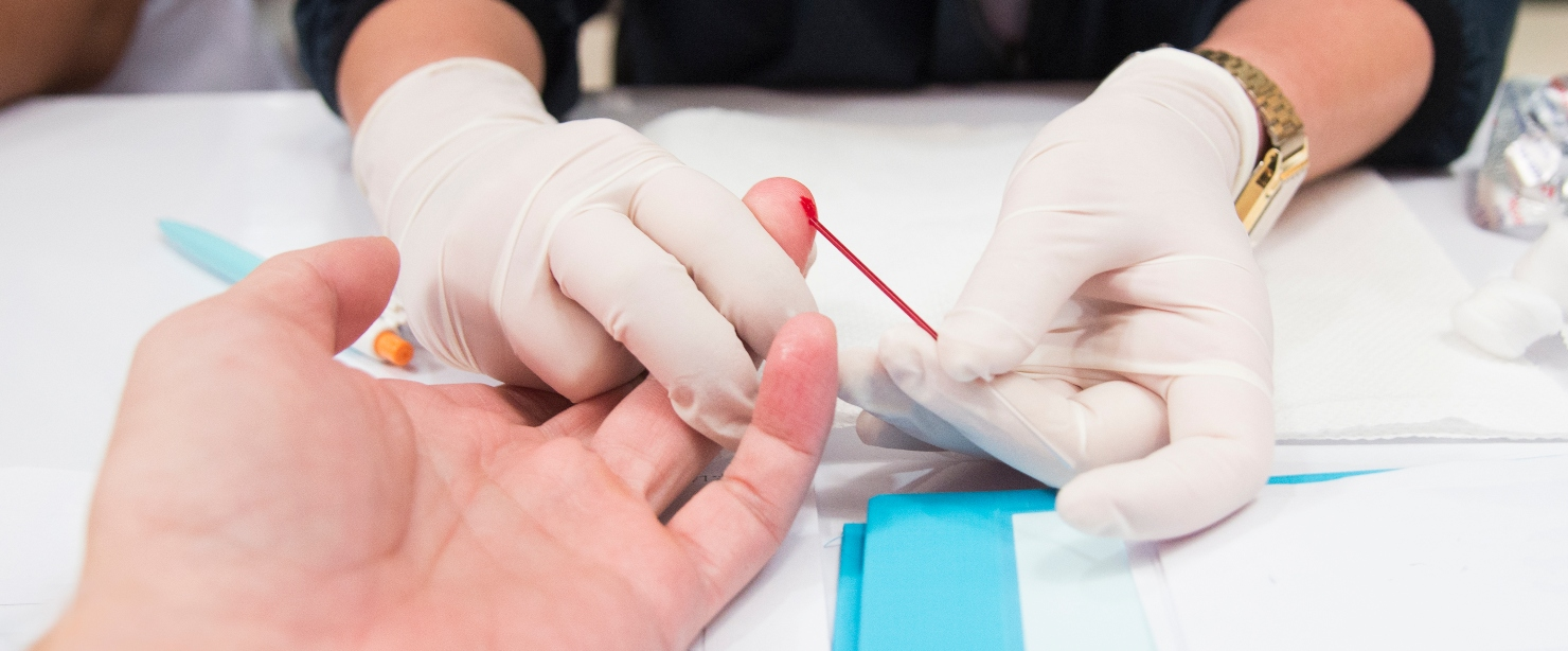 nurse performing finger prick antibody test