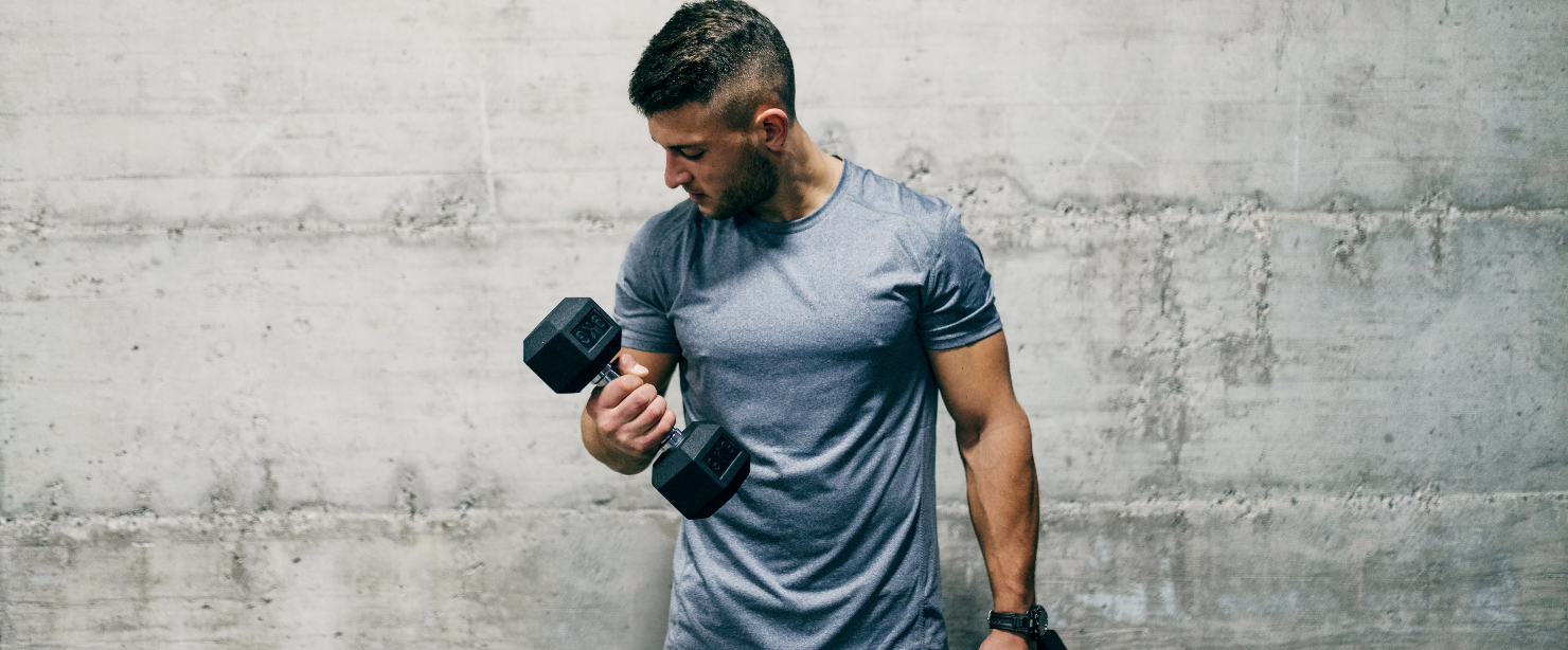 man curling dumbbells in front of concrete wall