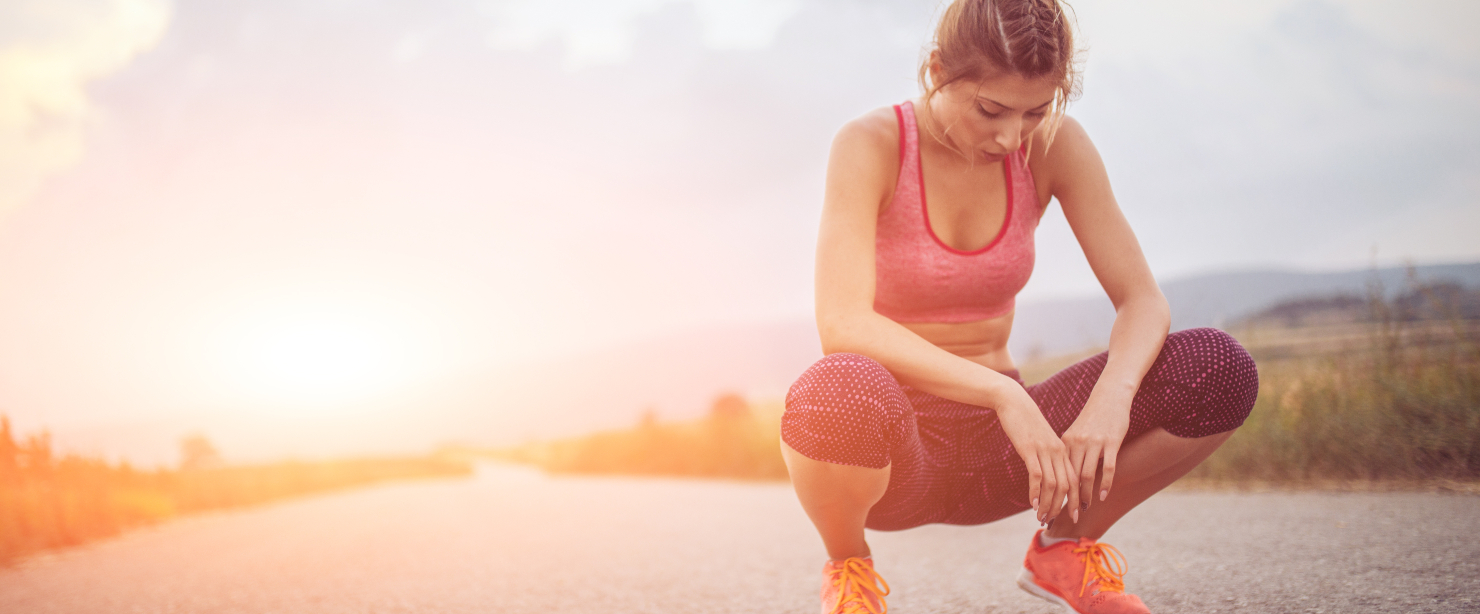 fit young woman resting during sunny hot workout outside