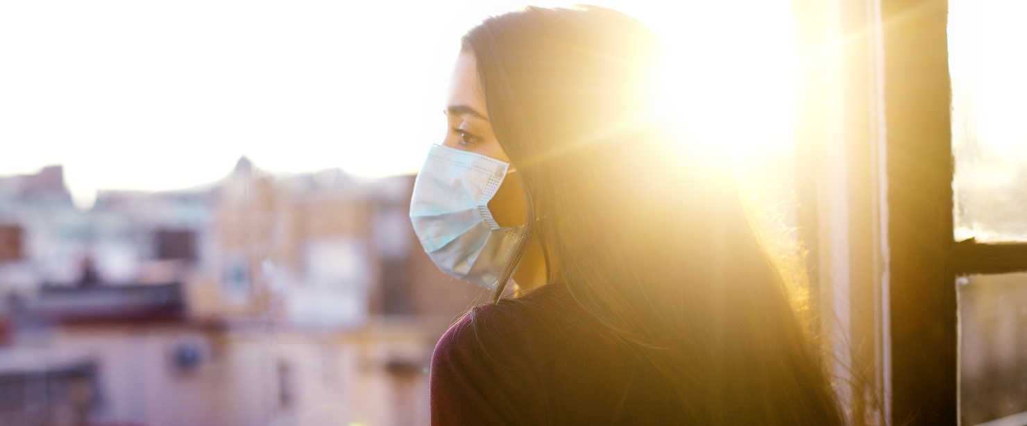 young girl looking out window at sun in a mask