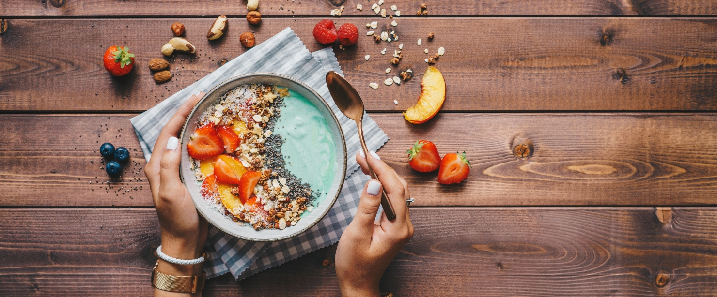 seed cycling: woman's hands holding smoothie bowl