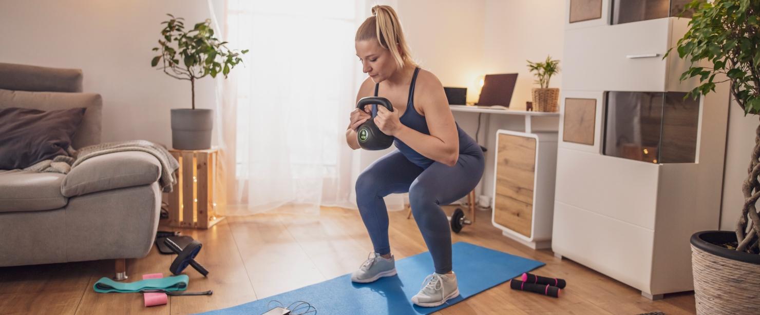 quick health goals: woman doing kettlebell squat at home