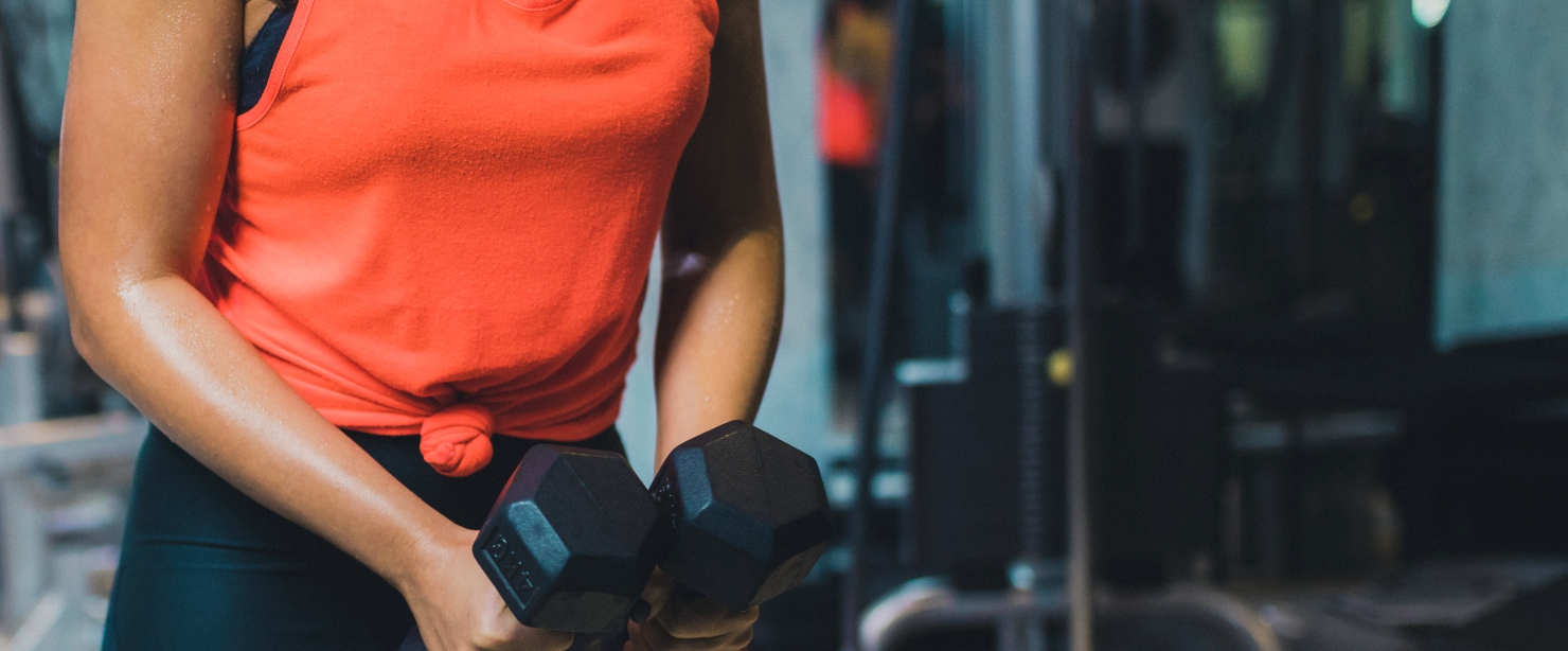the truth about toning: woman holding dumbbells in gym