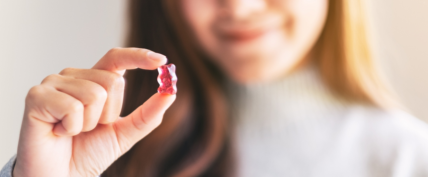 woman holding gummy supplement in her hand