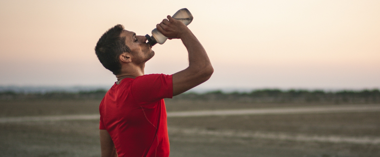 people who need more electrolytes: active man drinking sports drink outside