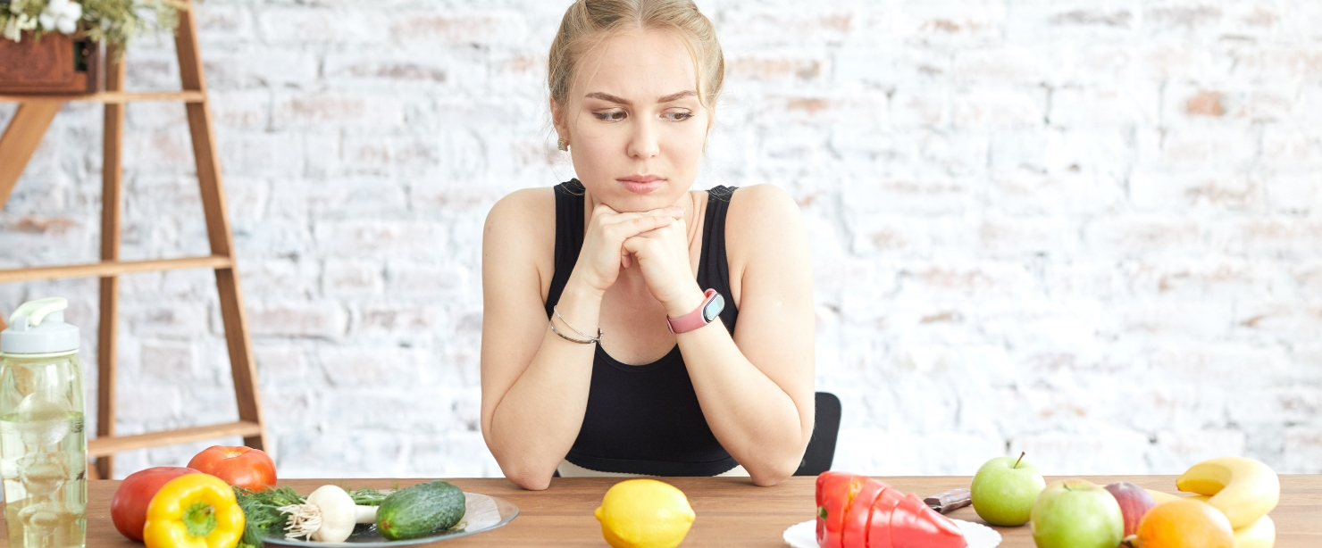 sad girl looking at table of produce