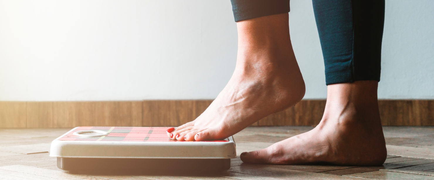 gaining weight on fitness journey: feet stepping onto scale